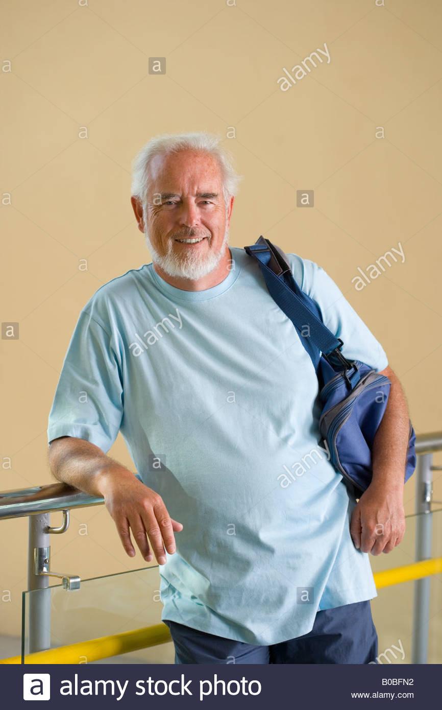 c36ff632cc7 Senior man with gym bag over shoulder, leaning on railing, smiling, portrait