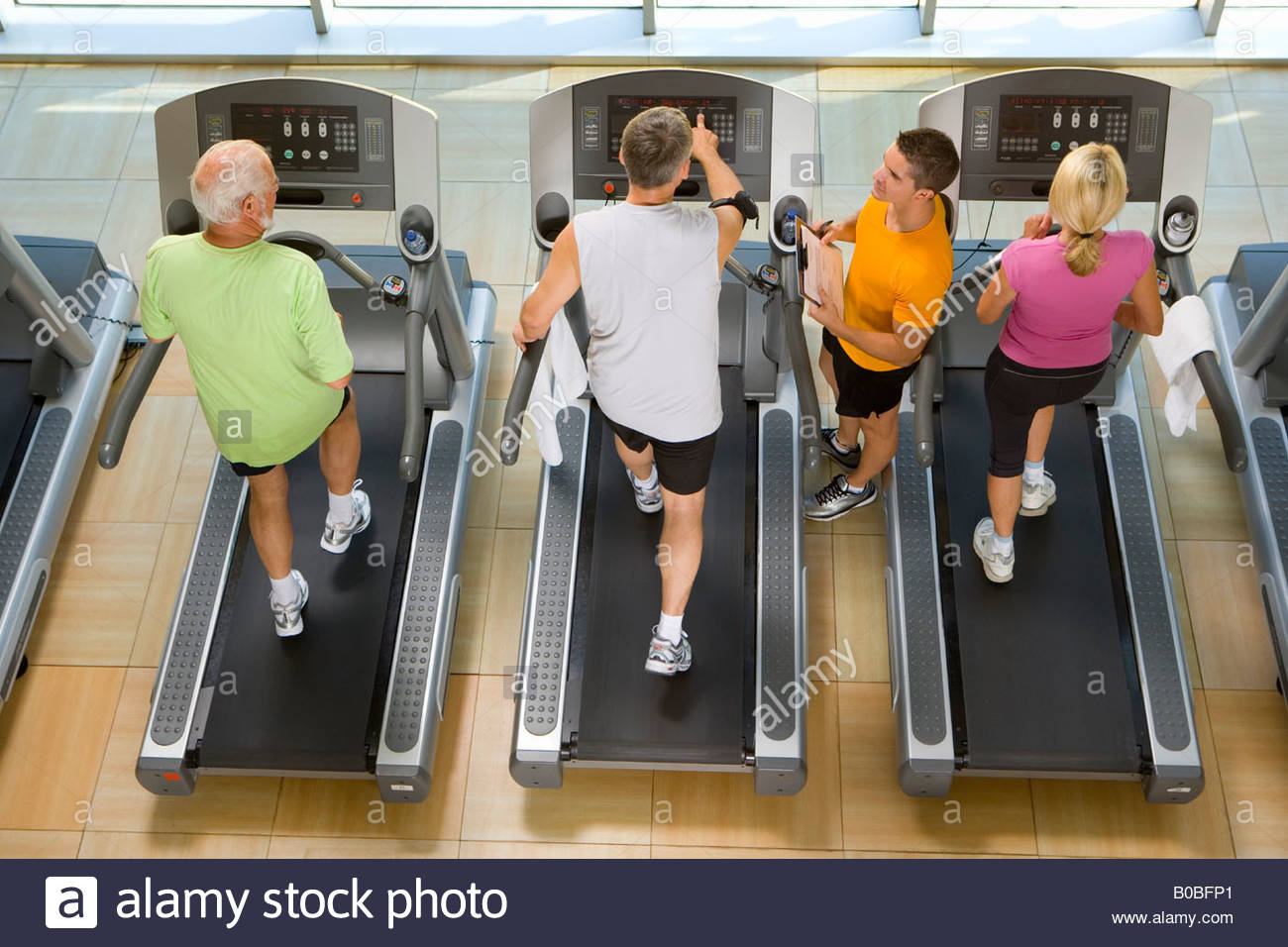 Man being trained in gym, elevated view - Stock Image