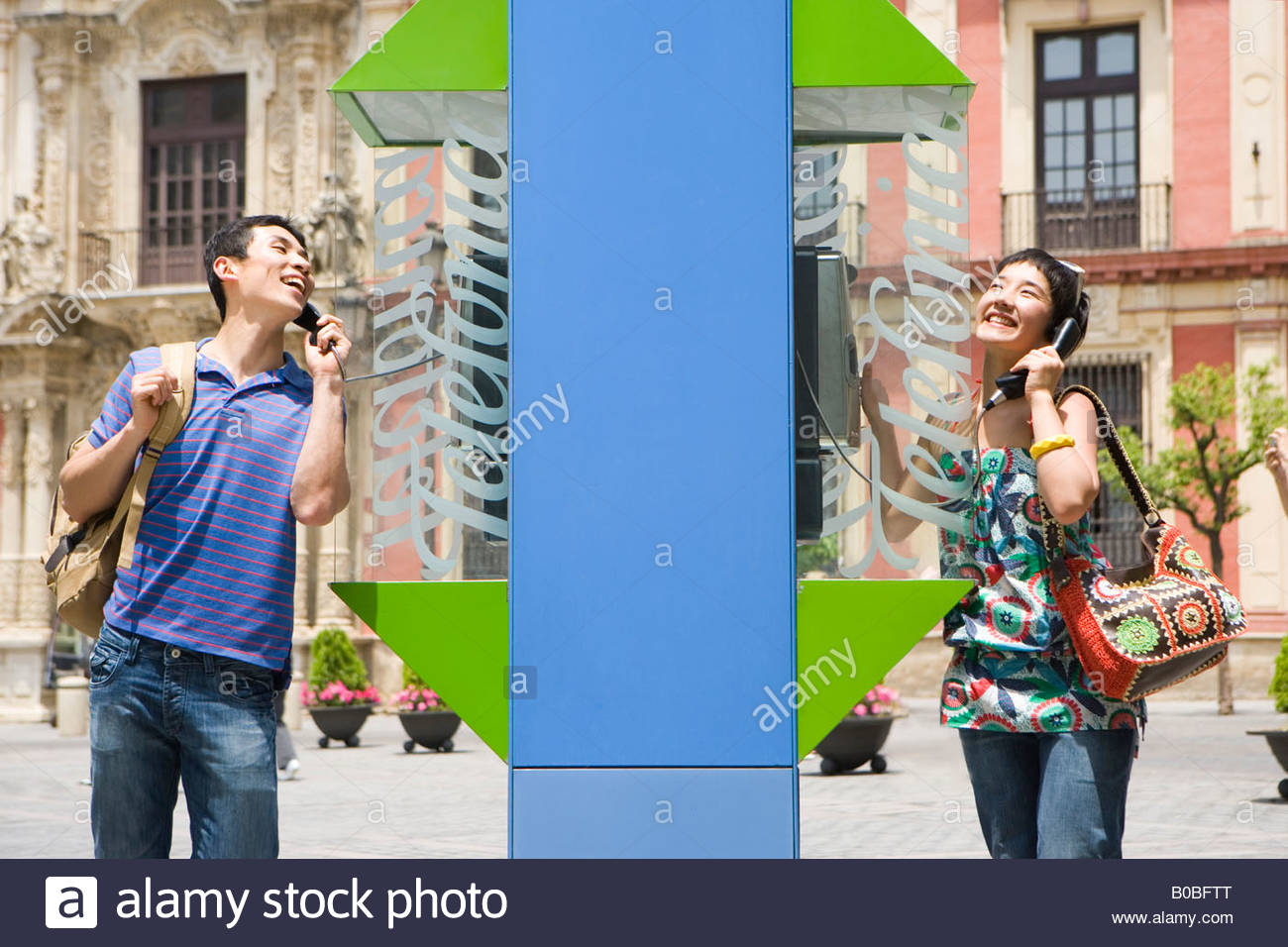 Man and woman by telephone booths using telephones, smiling - Stock Image