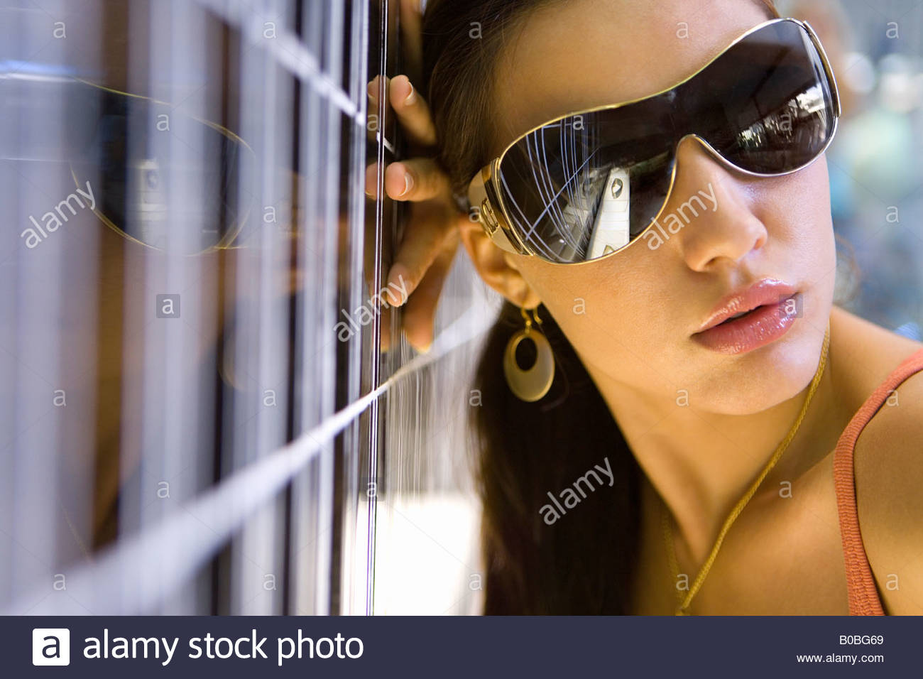 Young woman wearing sunglasses, leaning on wall, close-up - Stock Image