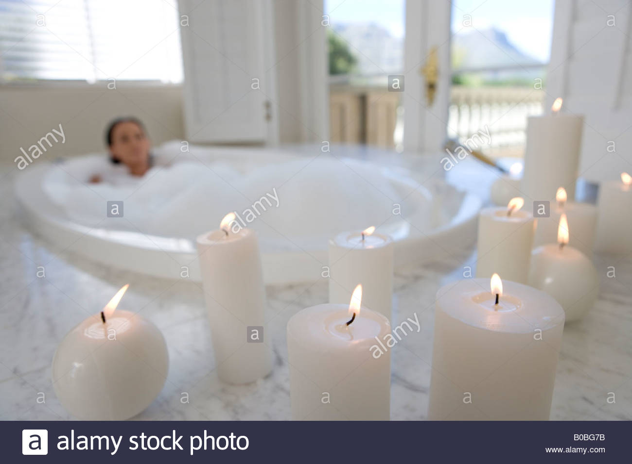 Young woman in bubble bath, illuminated candles in foreground - Stock Image