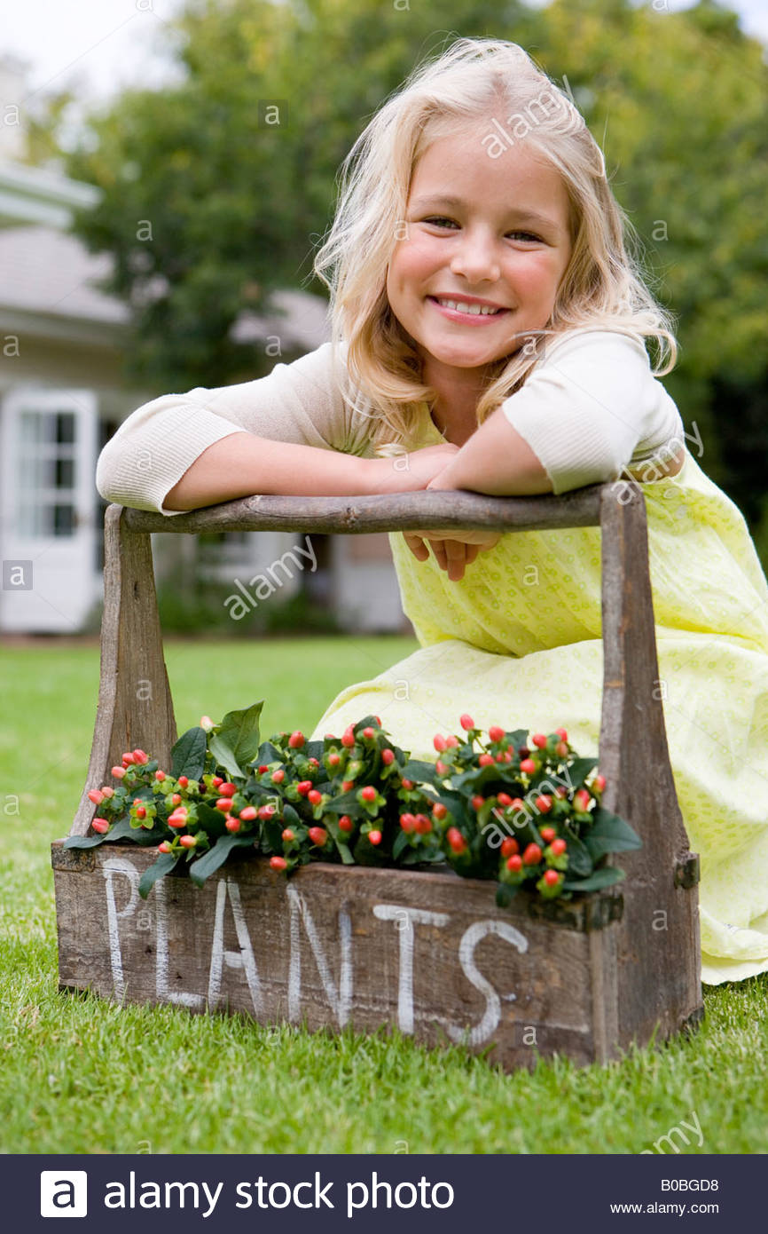 Girl  on grass leaning on handle of plant box, 'plants' written on box, smiling, portrait Stock Photo