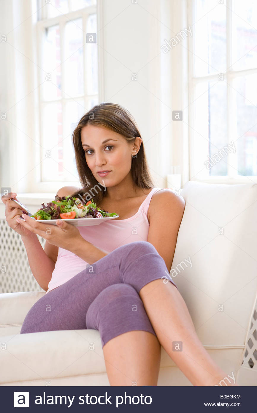 Young woman eating salad on sofa, legs crossed, portrait - Stock Image