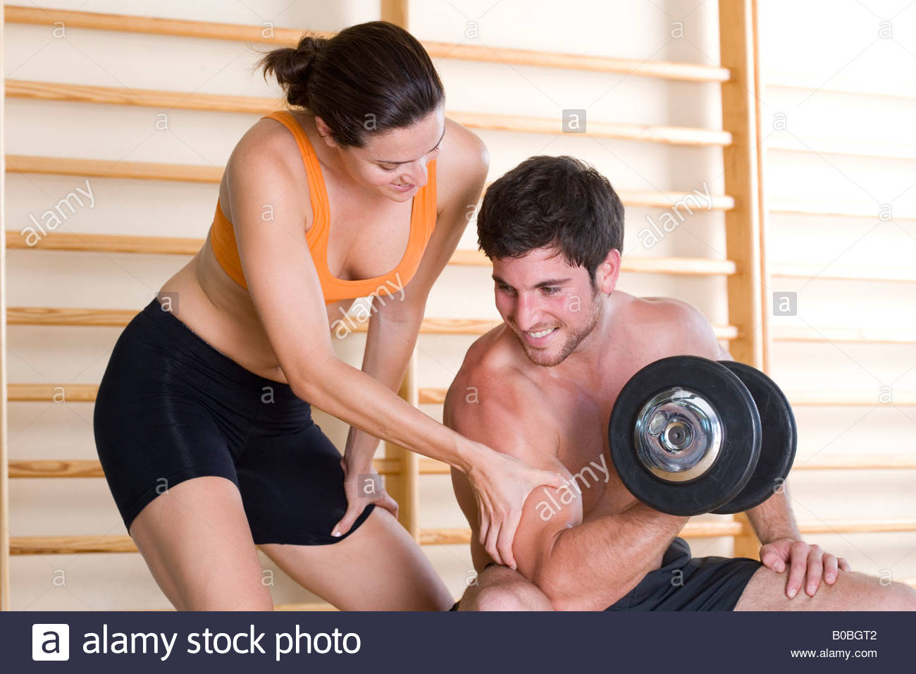 Woman feeling biceps of man using dumbbell, close-up - Stock Image