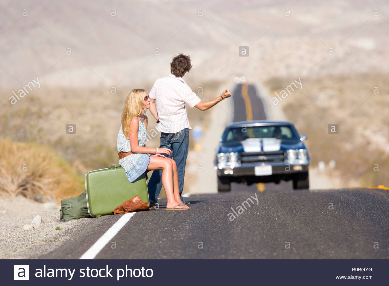 Hitchhikers By Side Of Road >> Young Couple Hitchhiking On Desert Road Side View Stock Photo
