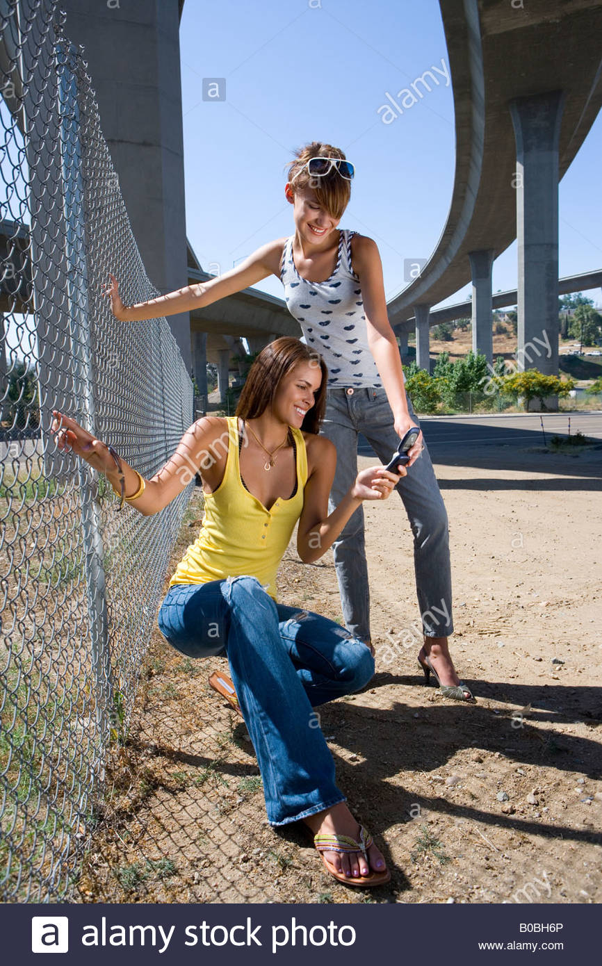 Two young women by fence beneath overpass, looking at mobile phone, smiling - Stock Image