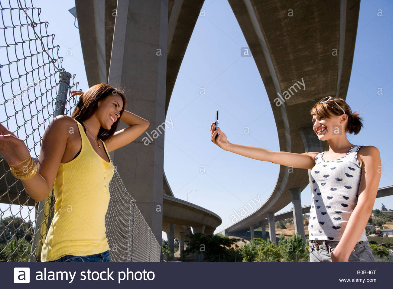 Young woman taking photograph of friend by fence beneath overpasses, low angle view - Stock Image