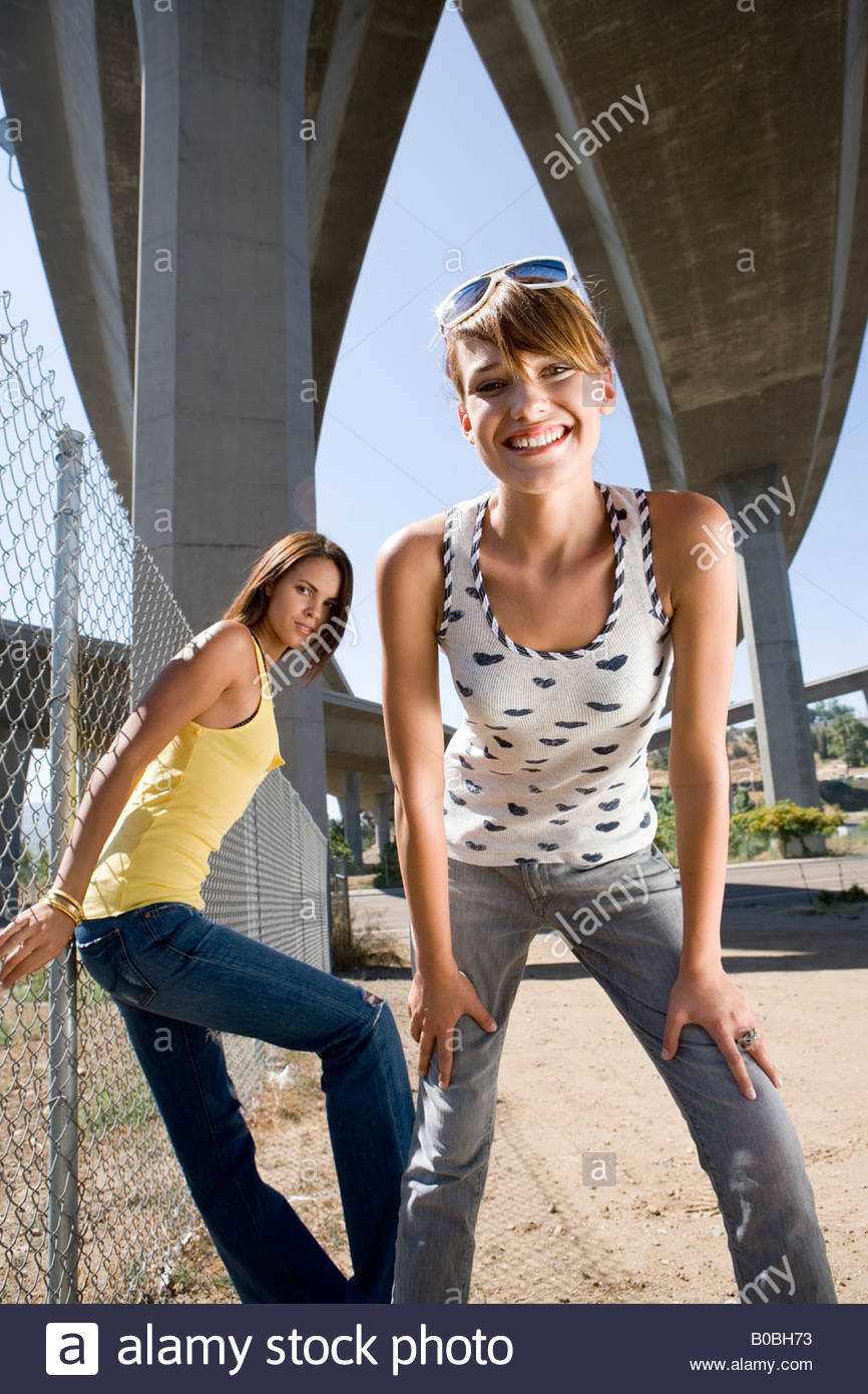 Young woman beneath overpasses, friend by fence, smiling, portrait, low angle view - Stock Image