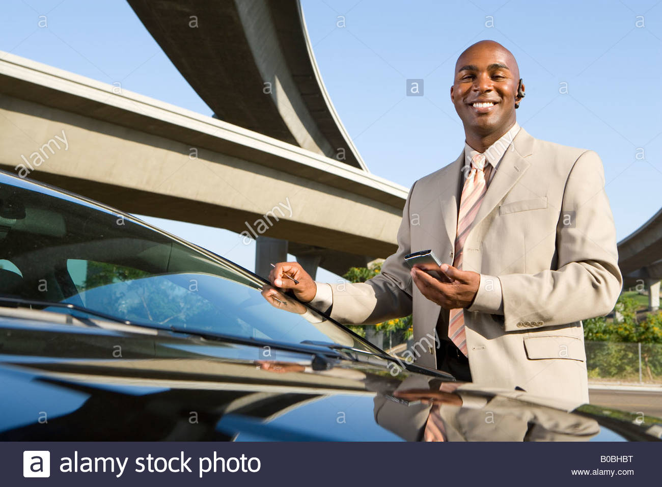 Businessman with electronic organiser by car and overpasses, portrait - Stock Image