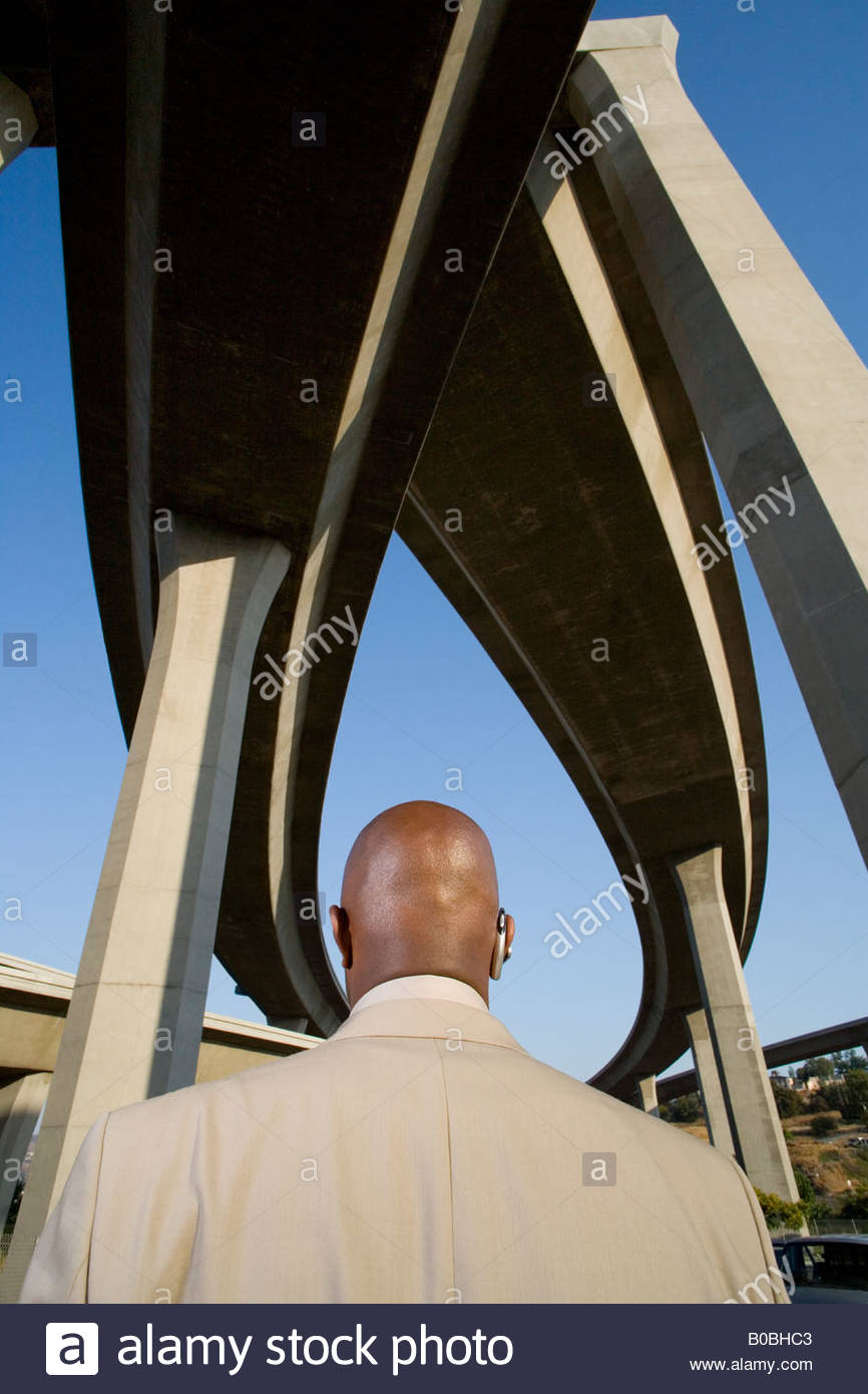 Businessman beneath overpasses, rear view - Stock Image
