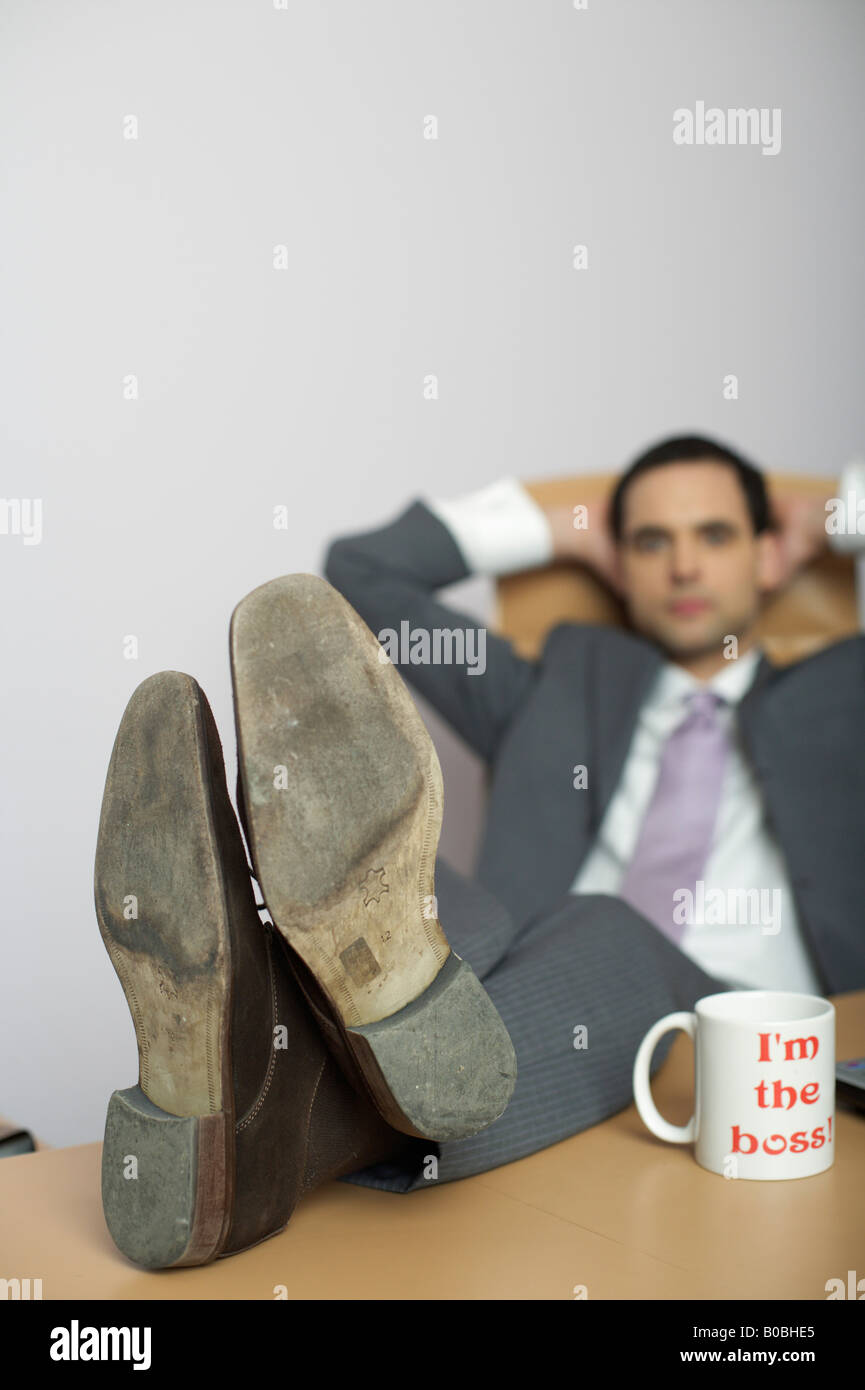 Businessman with feet on desk in office, coffee mug in foreground - Stock Image
