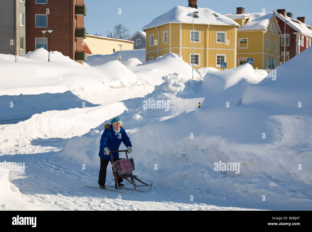 An elderly woman riding through the snow with a sleigh in the city centre of Kiruna / northern Sweden - Stock Image