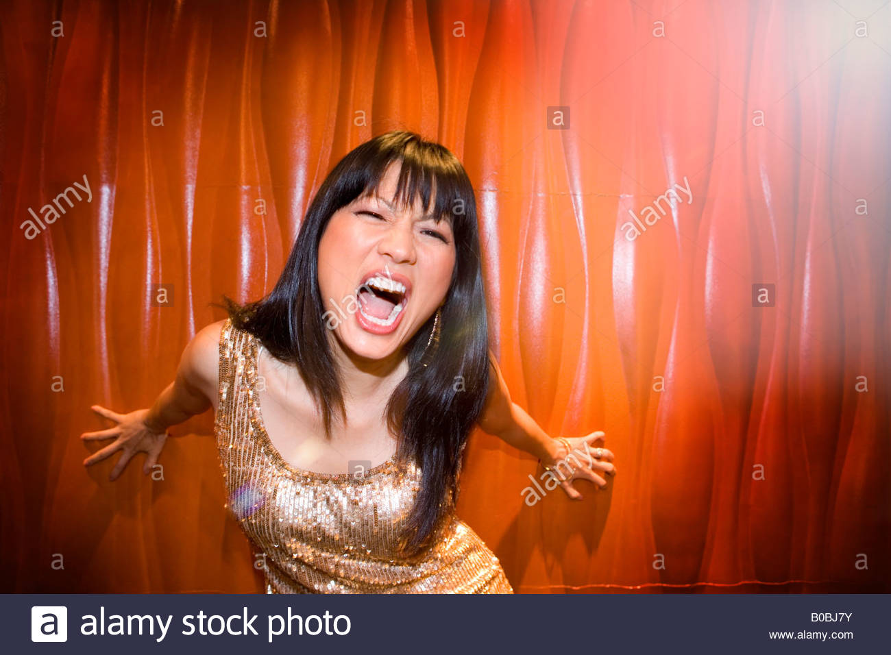 Young woman in spotlight making face, close-up - Stock Image