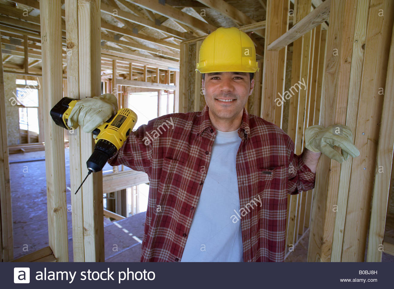 Builder in hardhat in partially built house, smiling, portrait - Stock Image