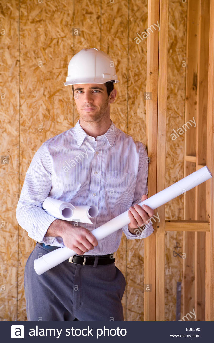 Architect with blueprints in hardhat in partially built house, portrait - Stock Image