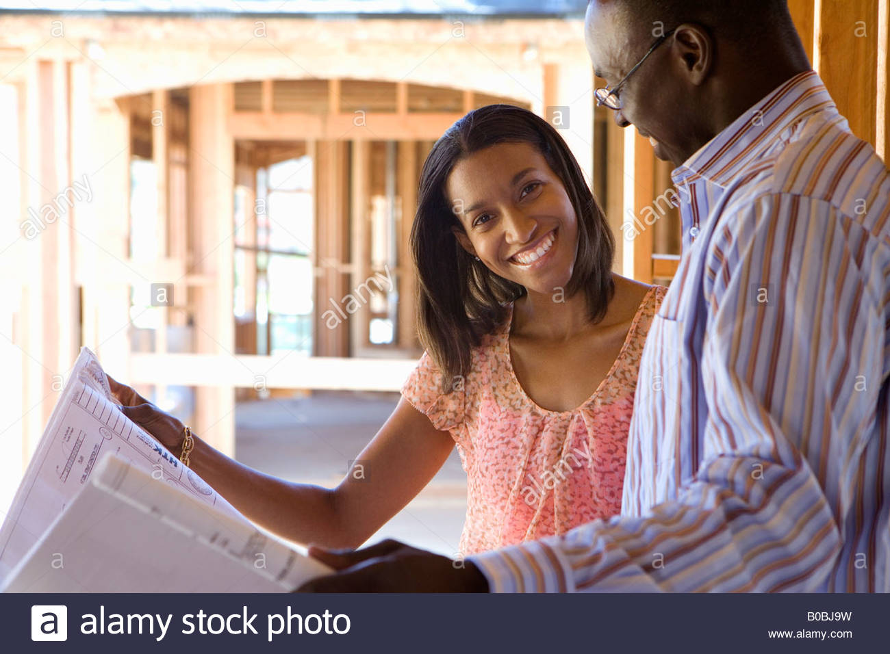 Young couple with blueprints in partially built house, smiling - Stock Image