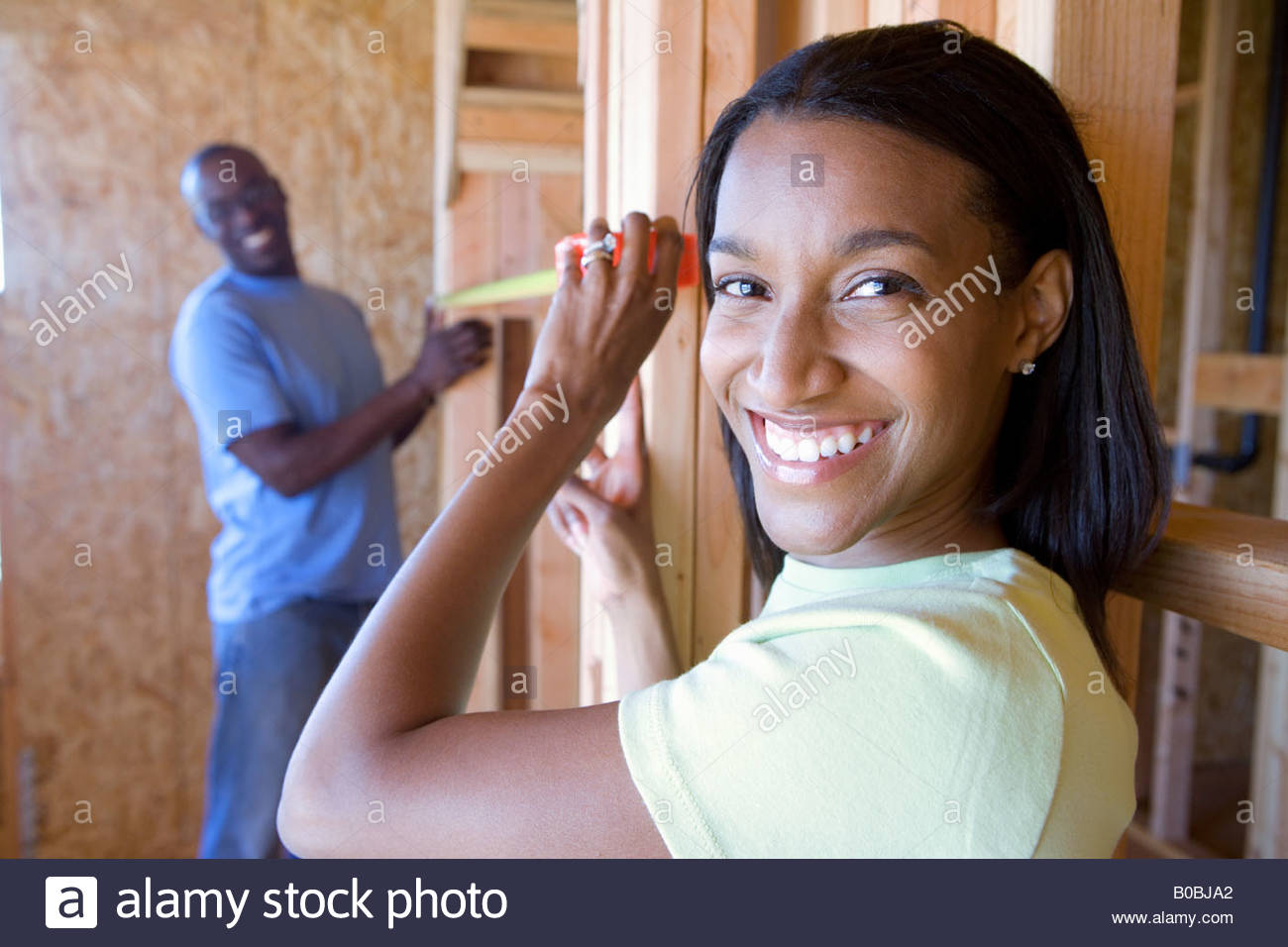 Young couple measuring wall in partially built house, smiling, portrait - Stock Image