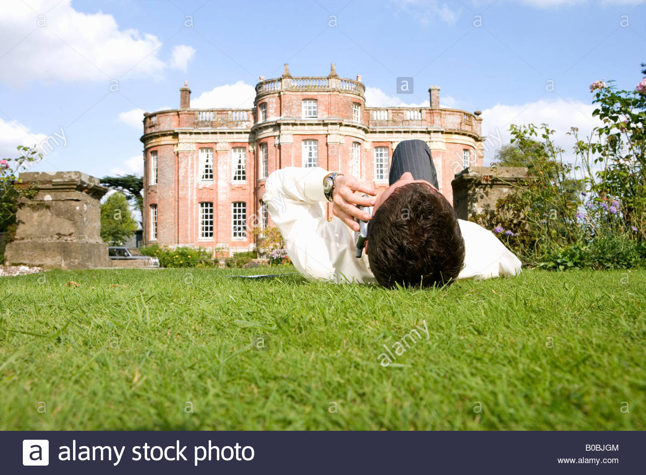 Young man lying on grass using mobile phone by manor house, ground view - Stock Image
