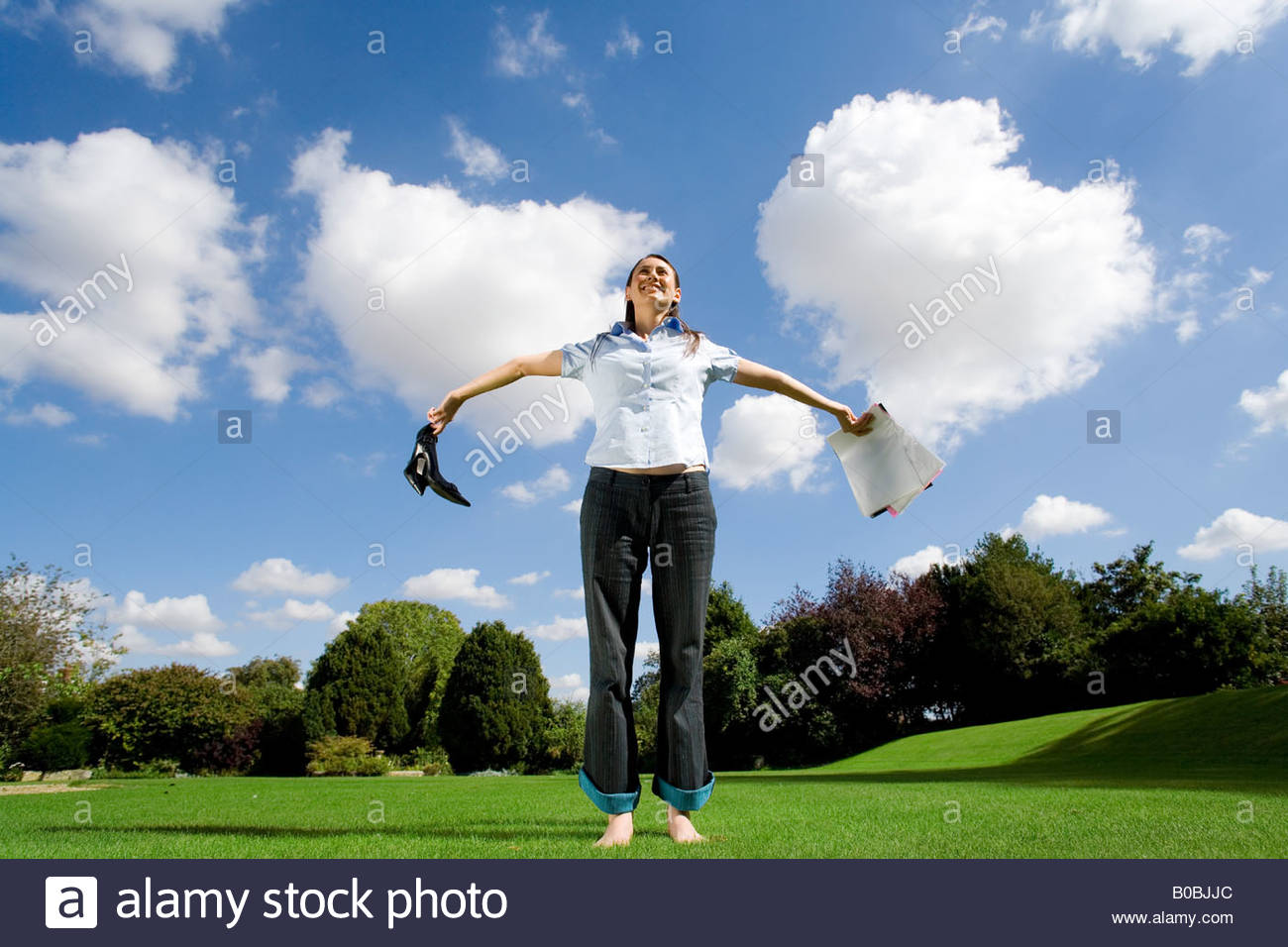 Woman on grass holding out paperwork and shoes, low angle view - Stock Image