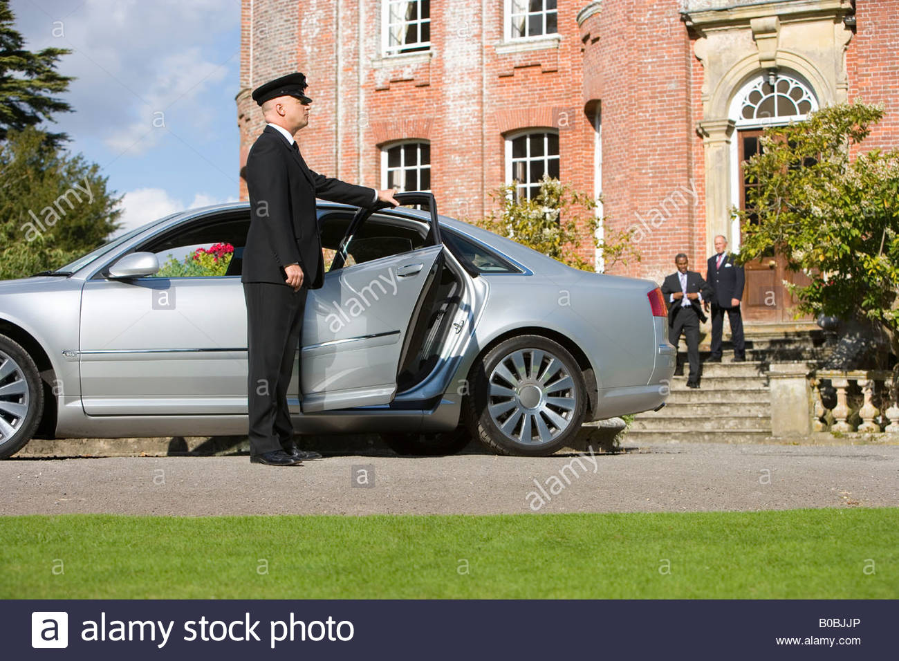 Chauffeur Holding Open Door Of Car By Manor House Businessmen In
