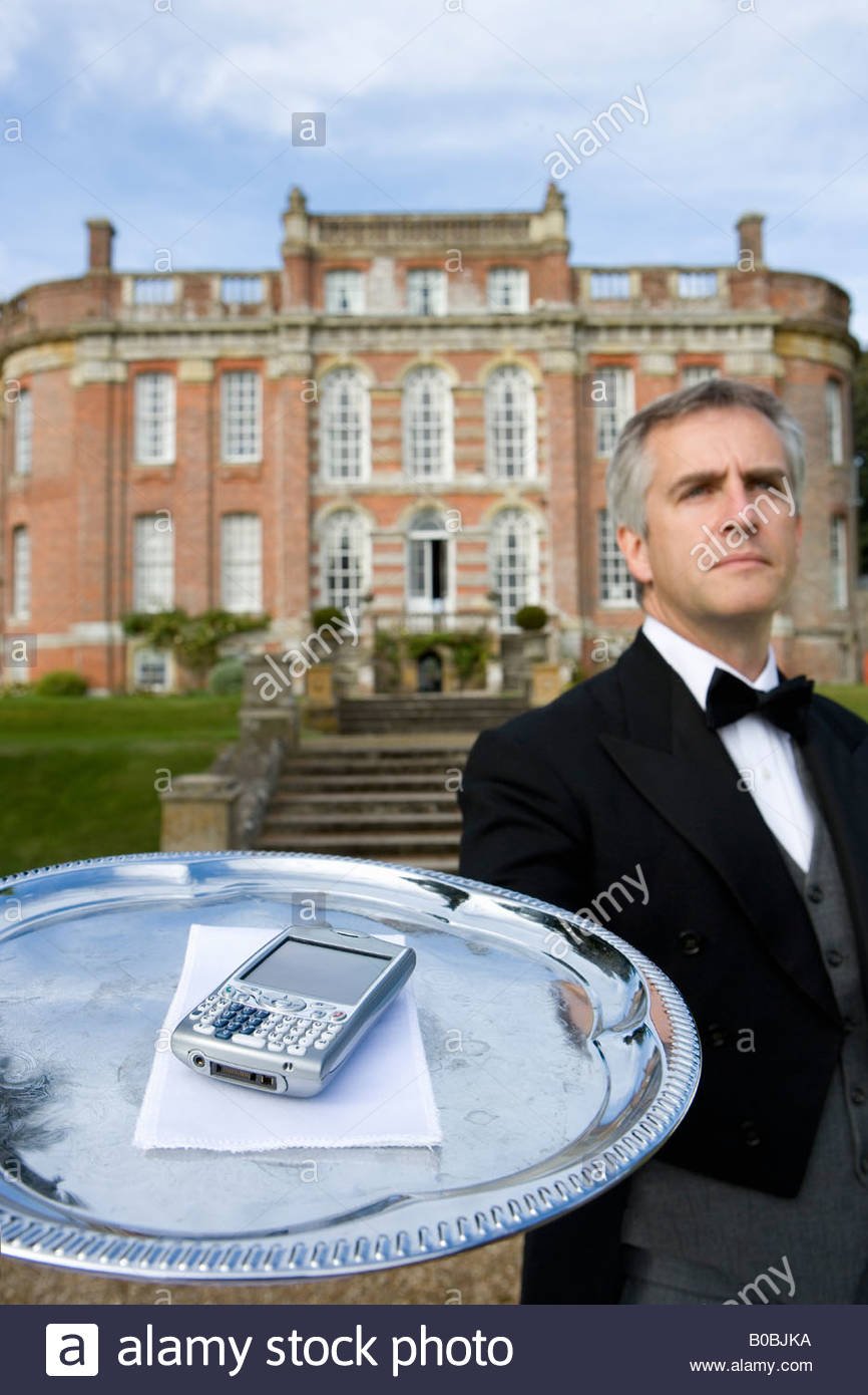 Mature butler with mobile phone on tray by manor house, low angle view - Stock Image
