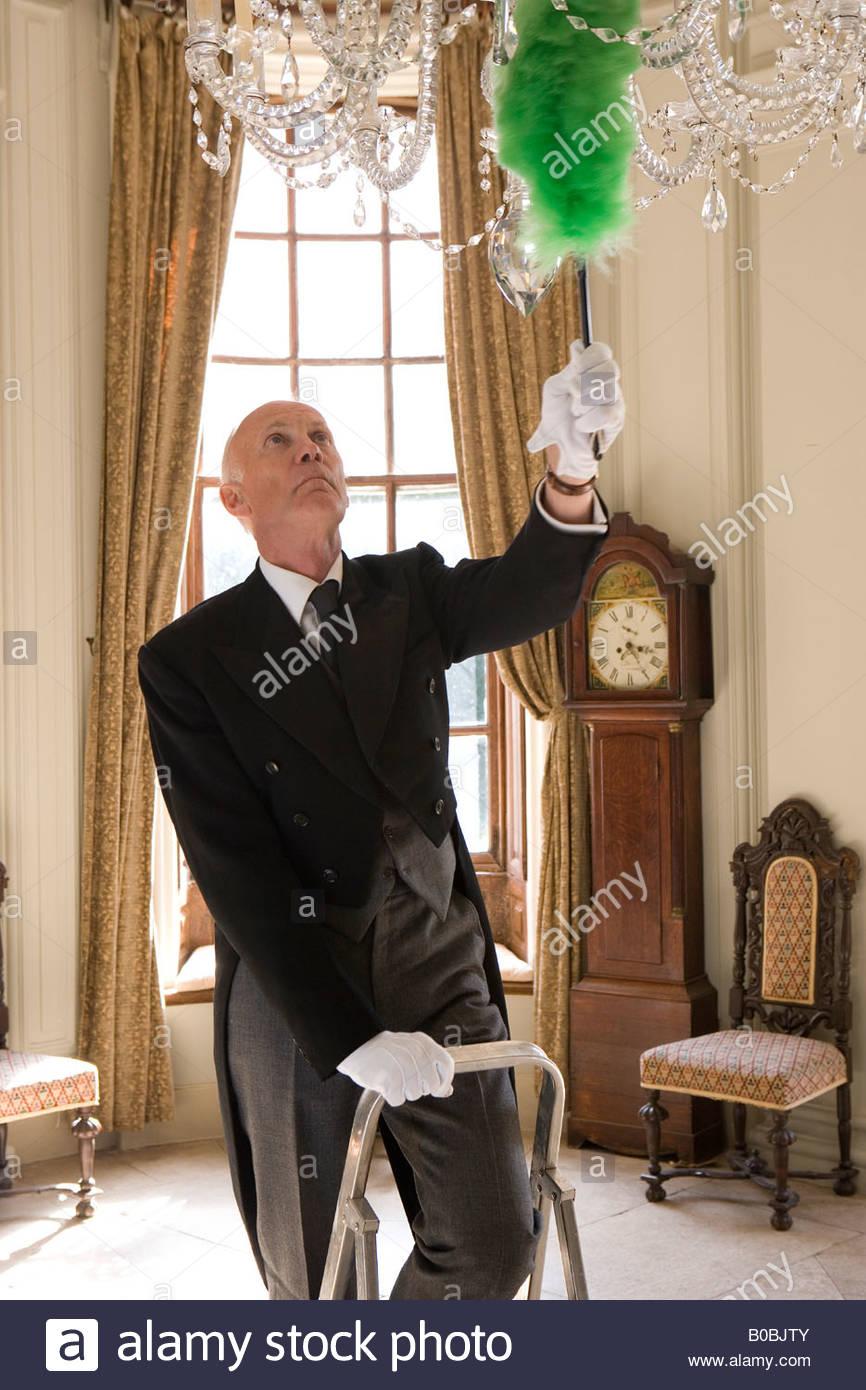 Butler on step ladder dusting chandelier - Stock Image