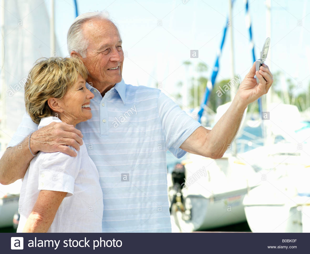 Senior couple arm in arm by boats, taking photograph of themselves, side view - Stock Photo