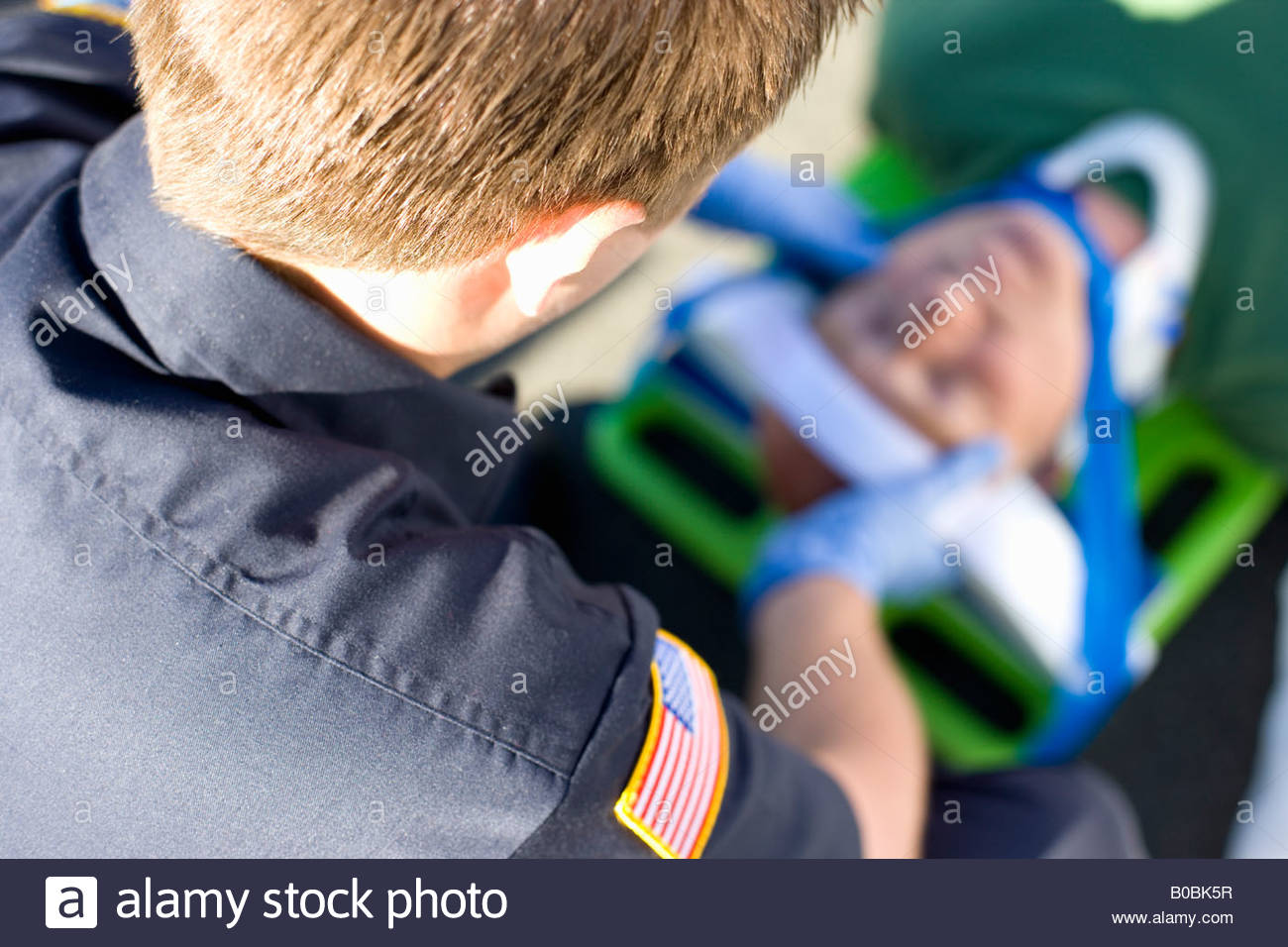 Paramedic helping man on stretcher with head in brace, elevated view - Stock Image