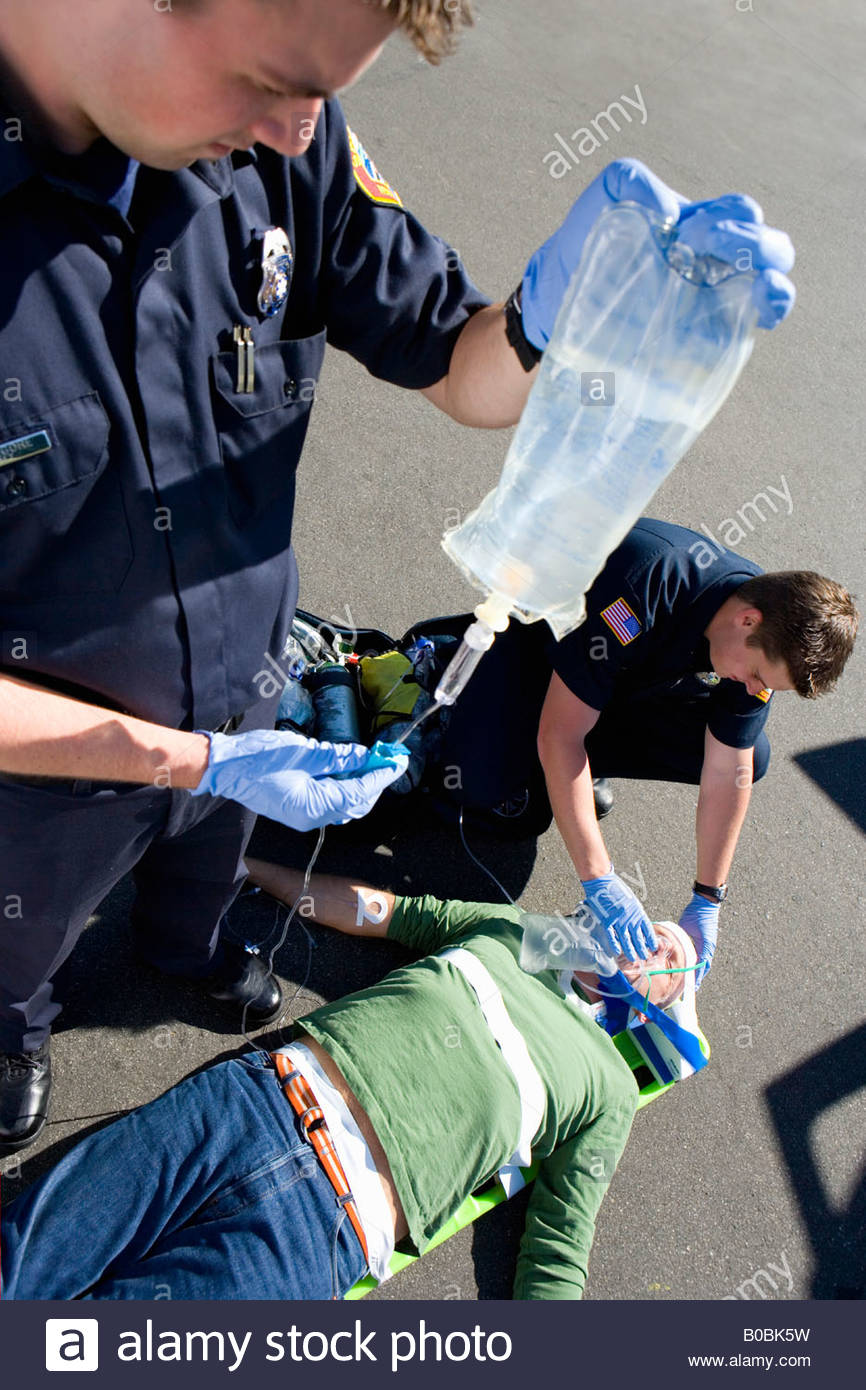 Paramedic and colleague helping man on stretcher, elevated view - Stock Image