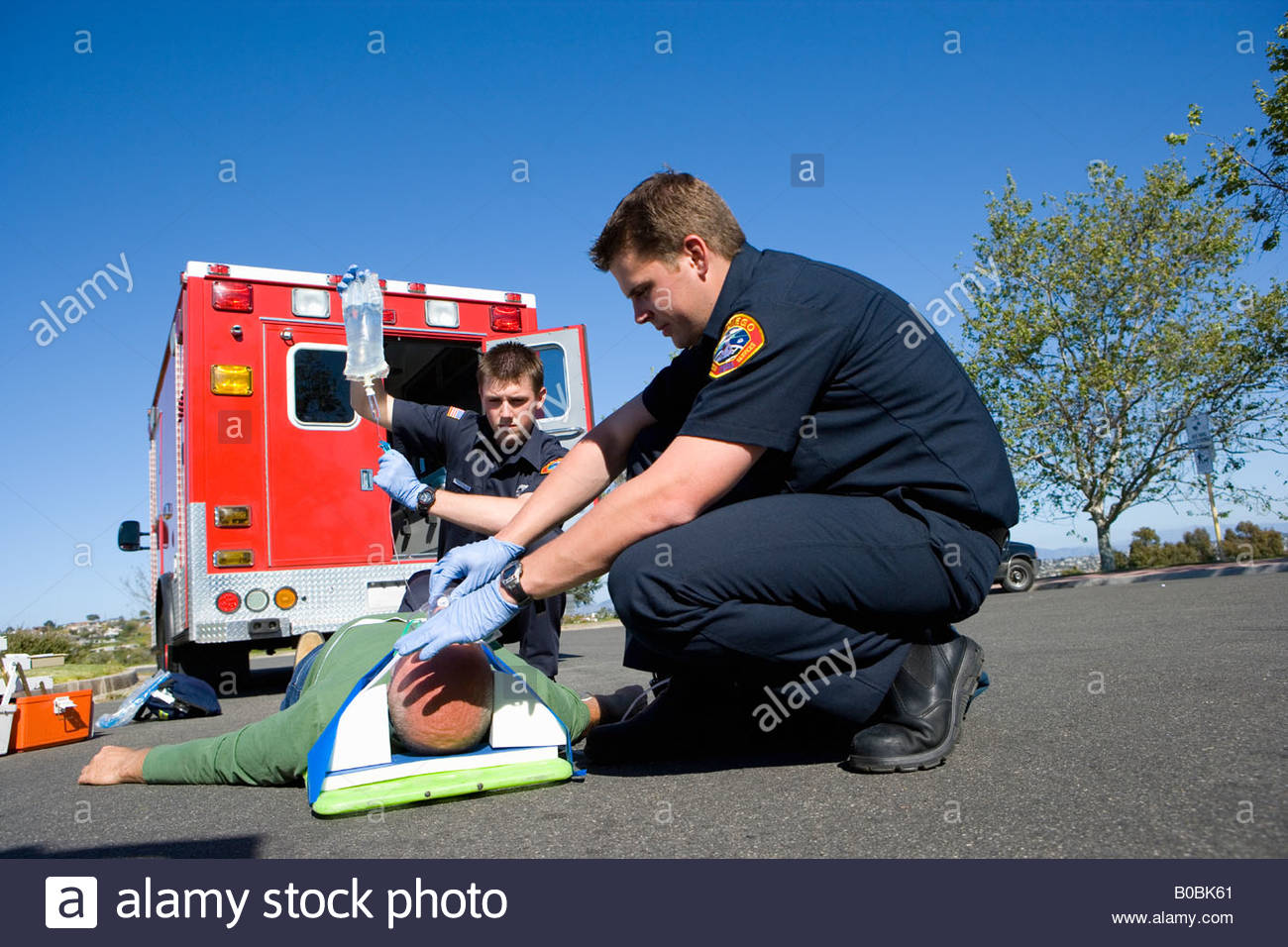 Paramedic and colleague helping man on stretcher, low angle view - Stock Image