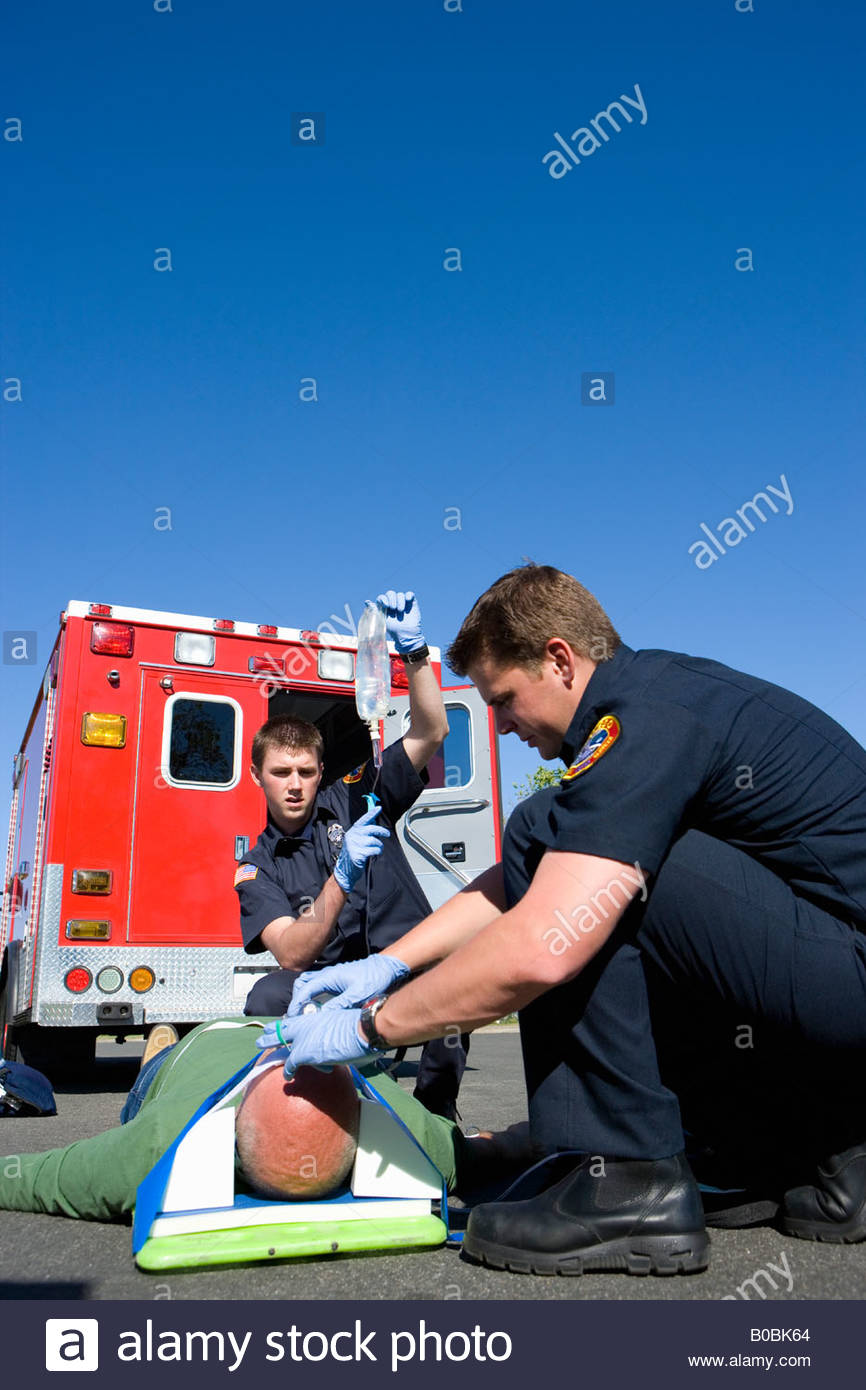 Paramedic and colleague helping man on stretcher by ambulance, low angle view - Stock Image
