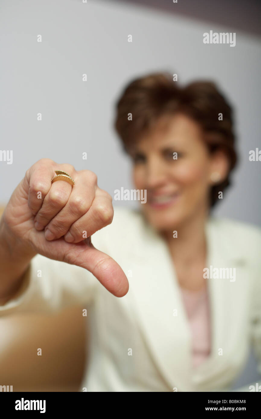 Businesswoman showing thumbs down - Stock Image