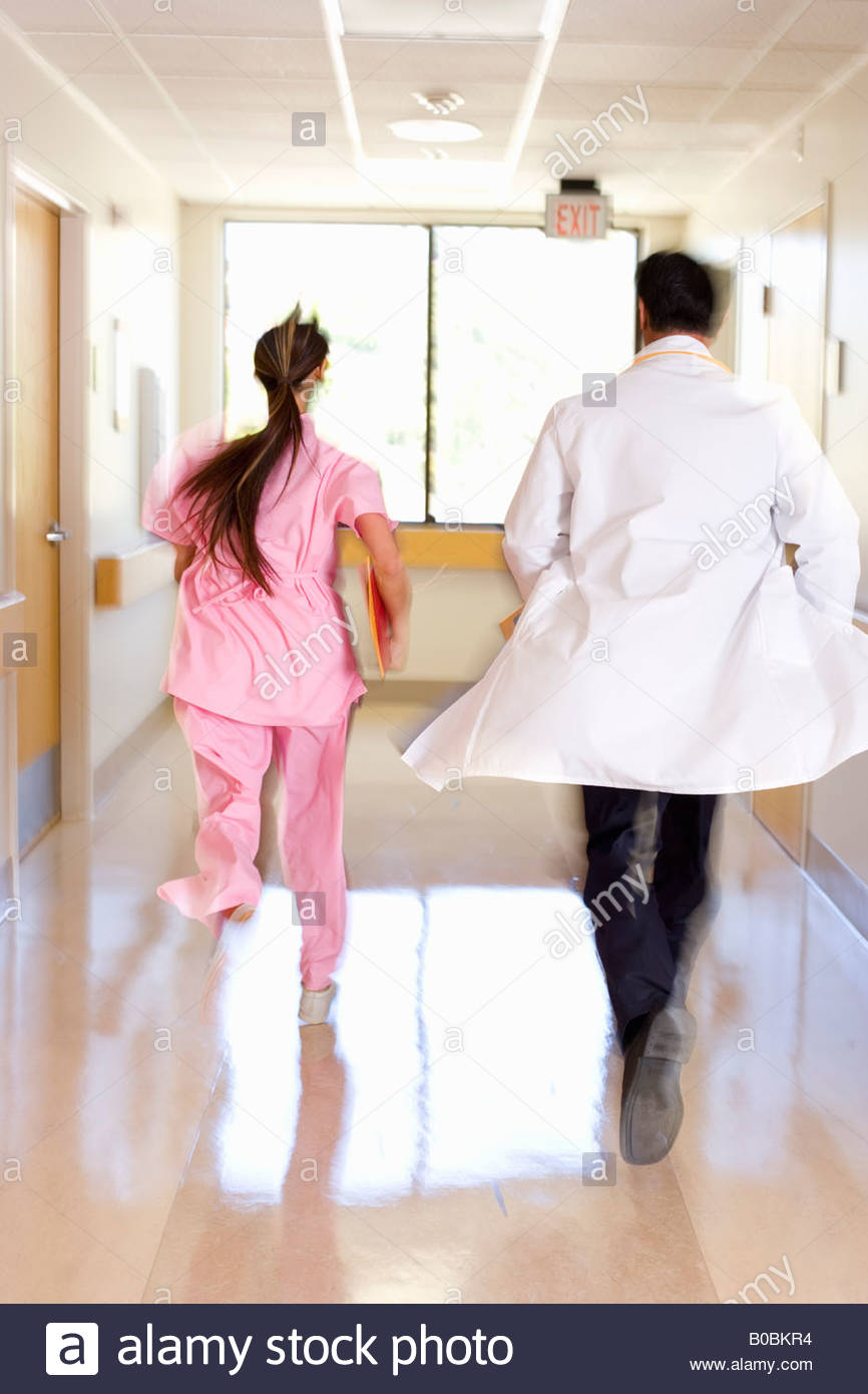 Doctor and nurse running in ward, rear view blurred motion - Stock Image