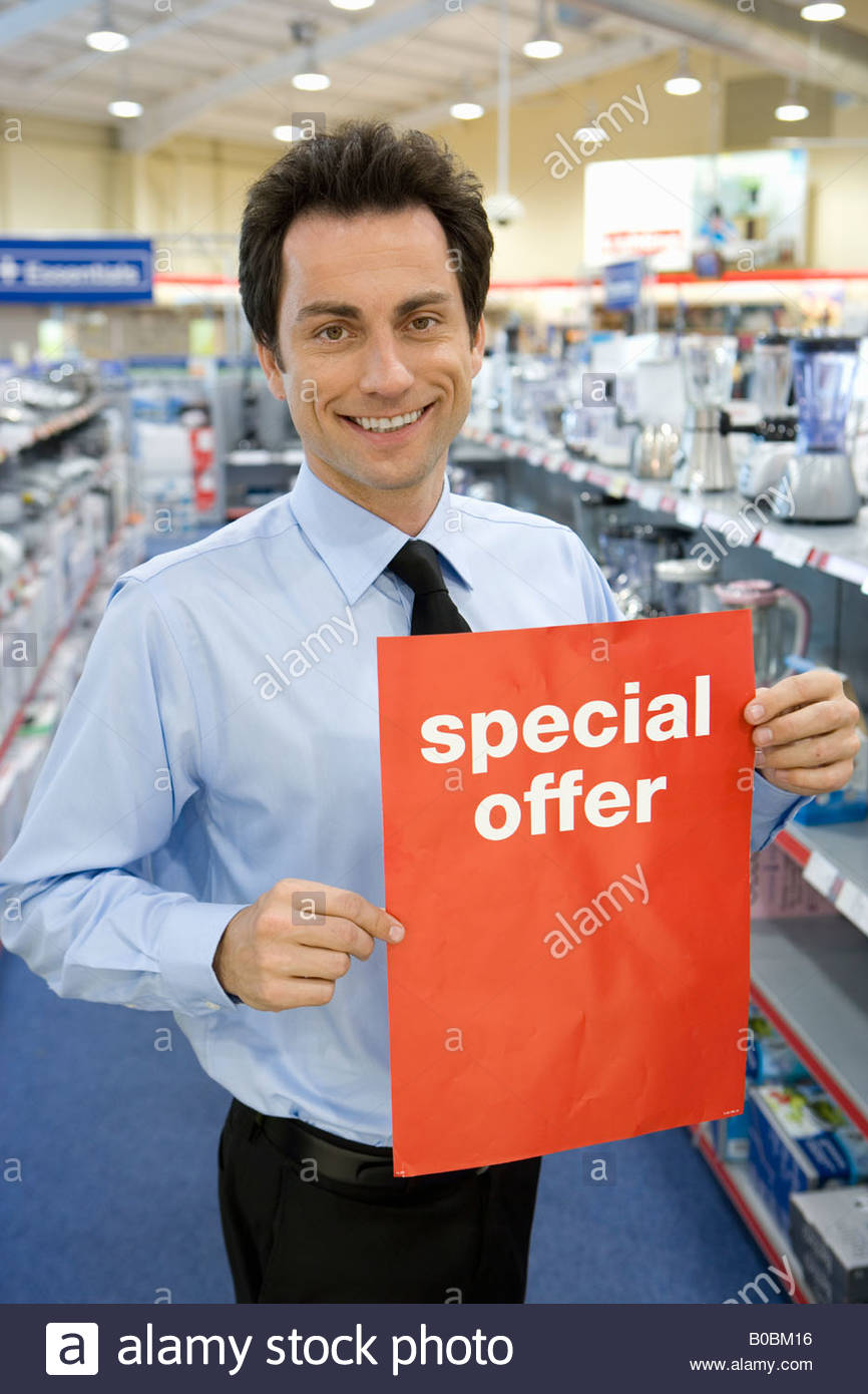Young salesman with 'special offer' sign in electronics aisle, smiling, portrait - Stock Image