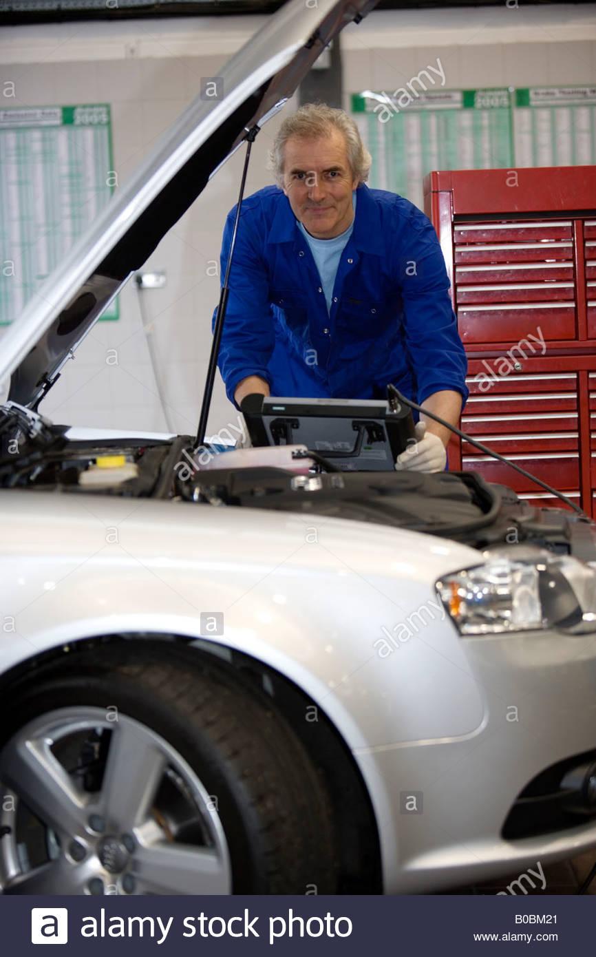 Mechanic with diagnostic computer by open bonnet of car, portrait, low angle view - Stock Image