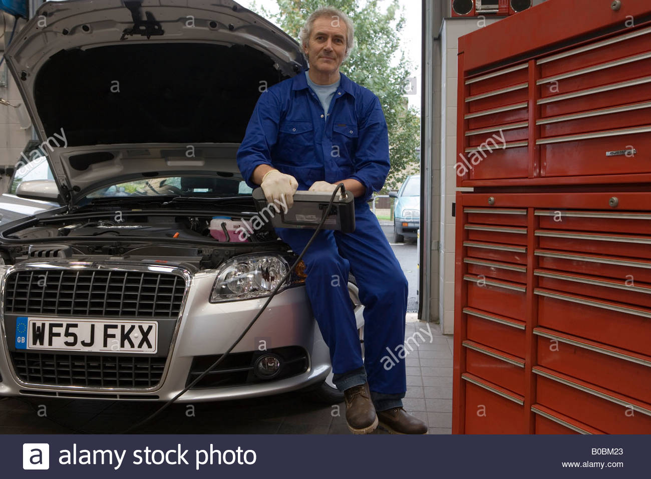 Mechanic with diagnostic computer on car with open bonnet, portrait, low angle view - Stock Image
