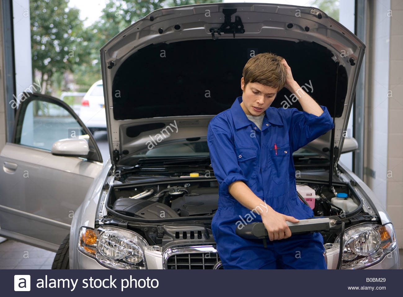 Female mechanic looking at diagnostic computer by open bonnet of car, hand to head - Stock Image