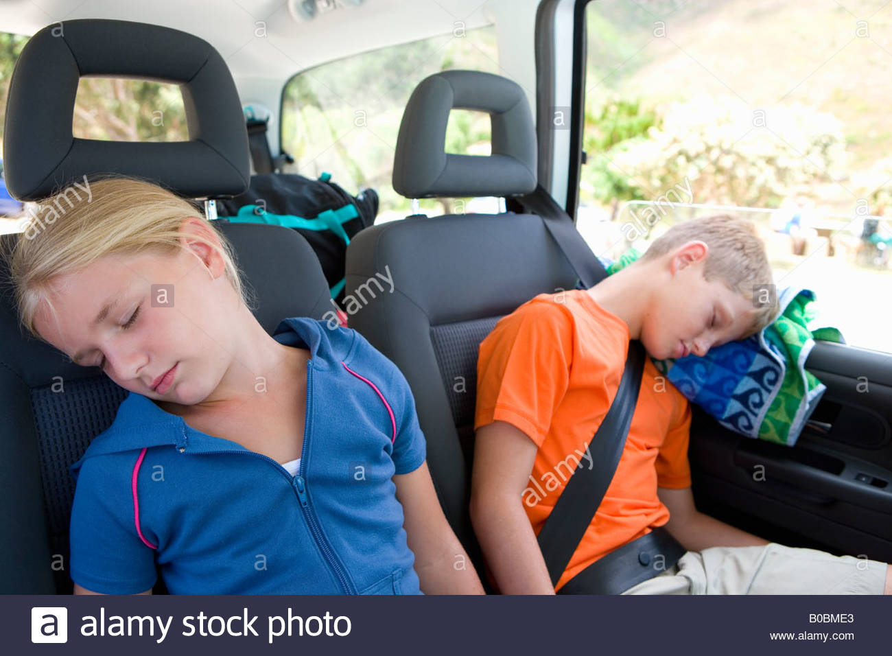 Brother and sister (8-12) asleep in back of car, close-up - Stock Image
