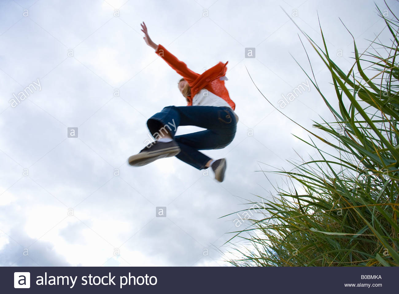 Girl 7-9 years jumping from grass outdoors, low angle view - Stock Image