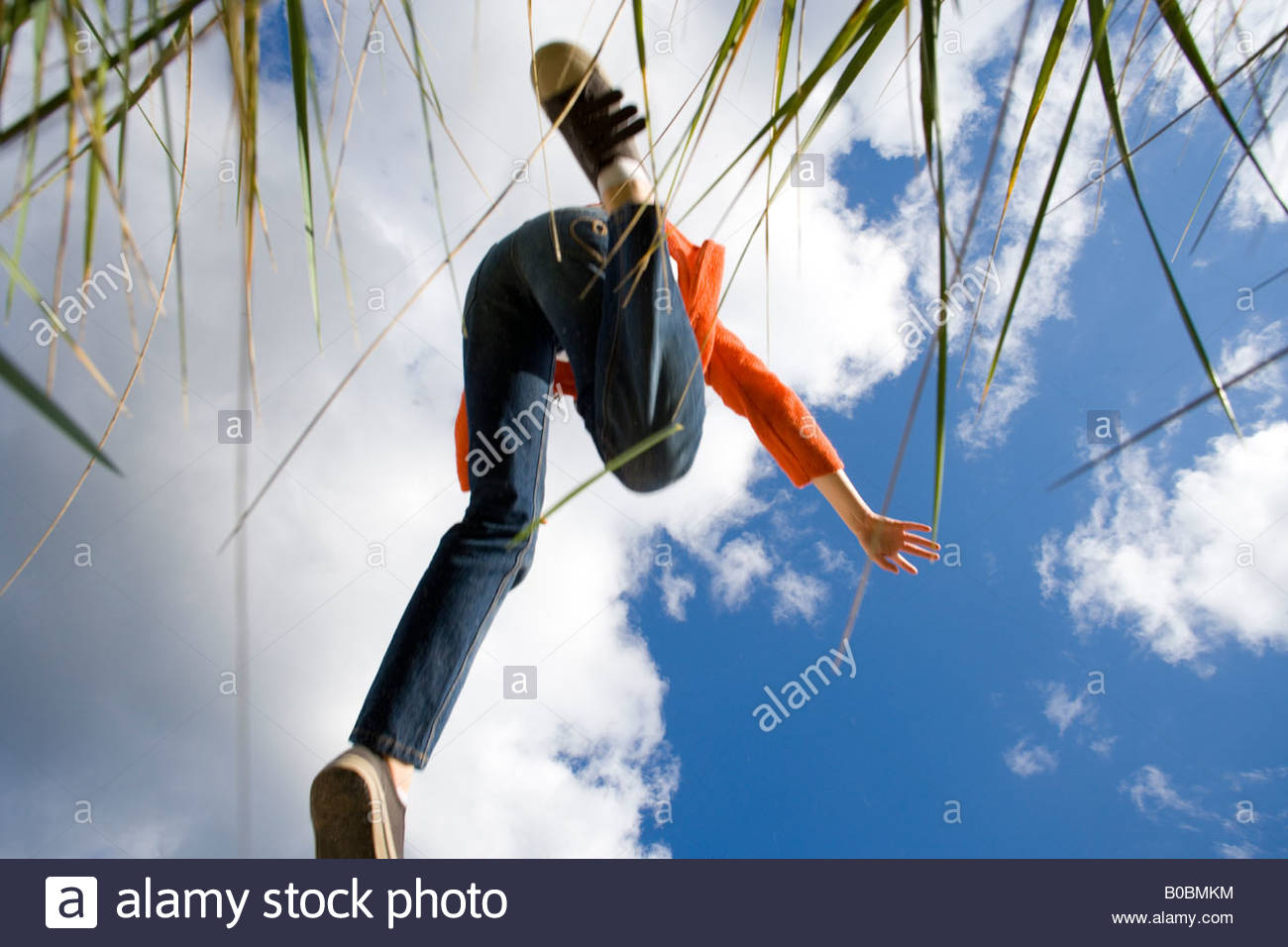 Boy 7-9 years jumping from grass outdoors, view from below - Stock Image
