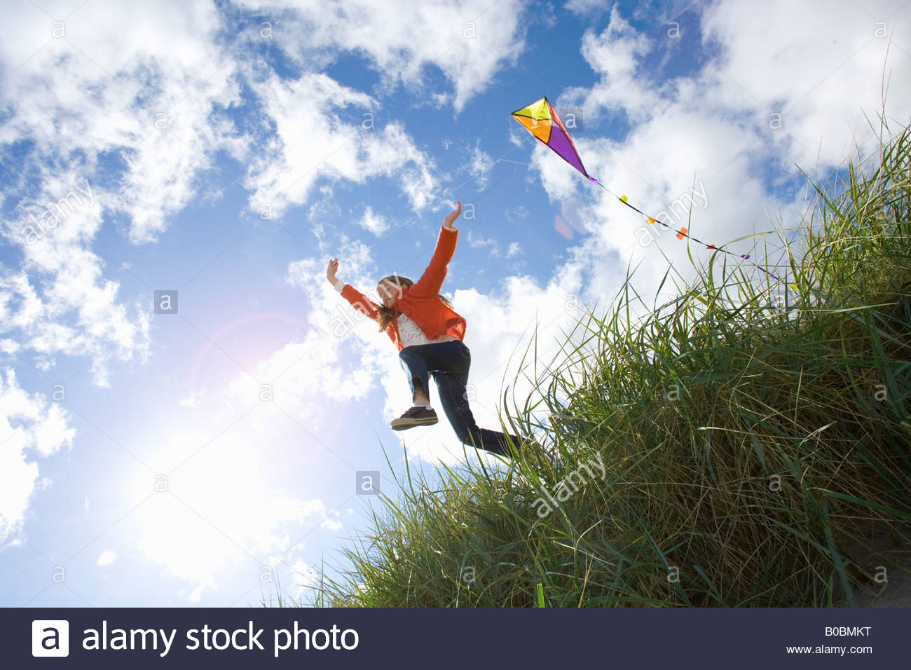 Girl 7-9 years flying kite outdoors, low angle view - Stock Image
