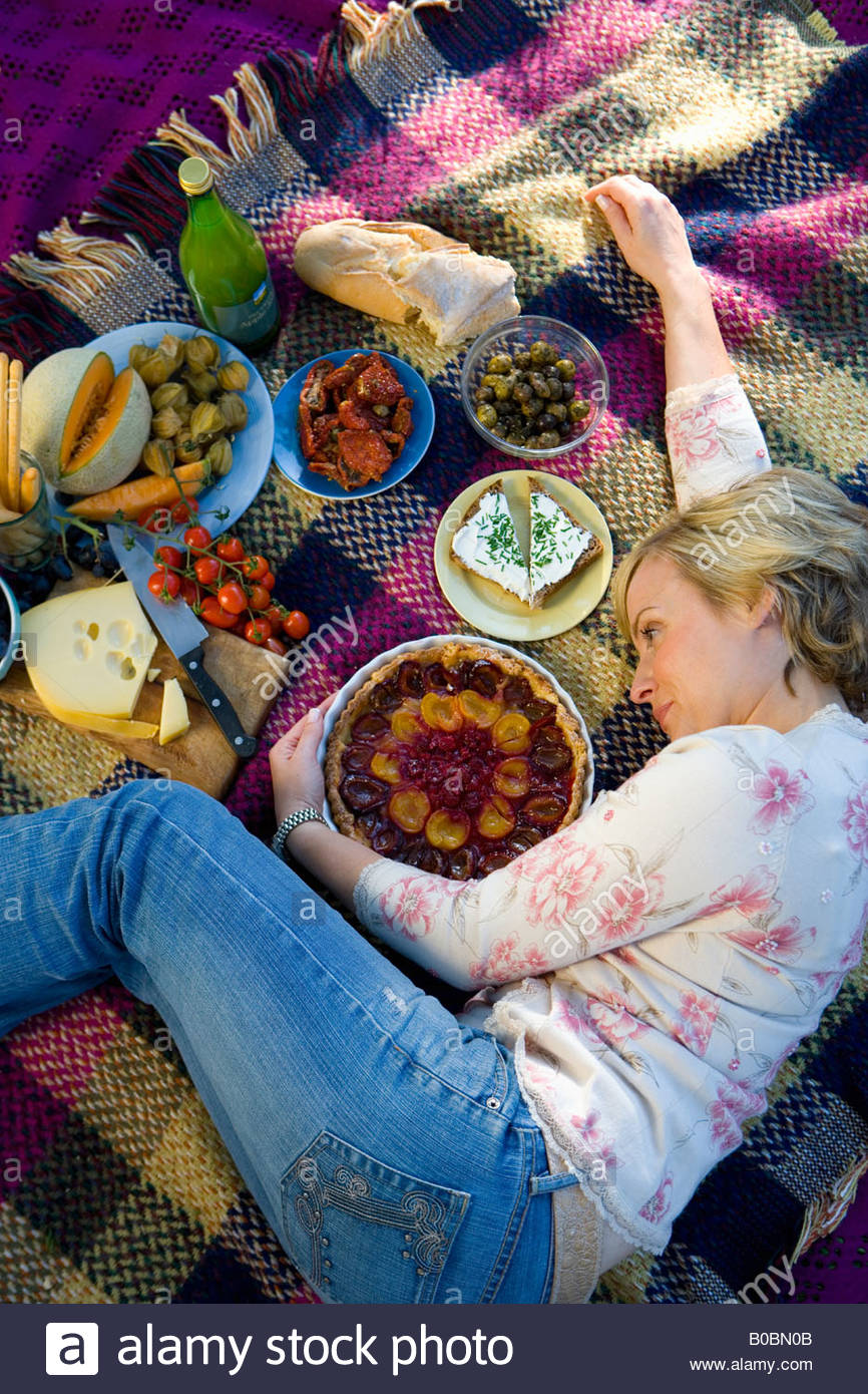 Woman on picnic blanket embracing tart, elevated view, full frame - Stock Image
