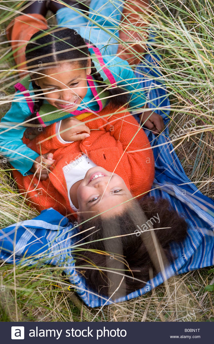 Sisters 5-9 lying in grass, smiling, elevated view - Stock Image