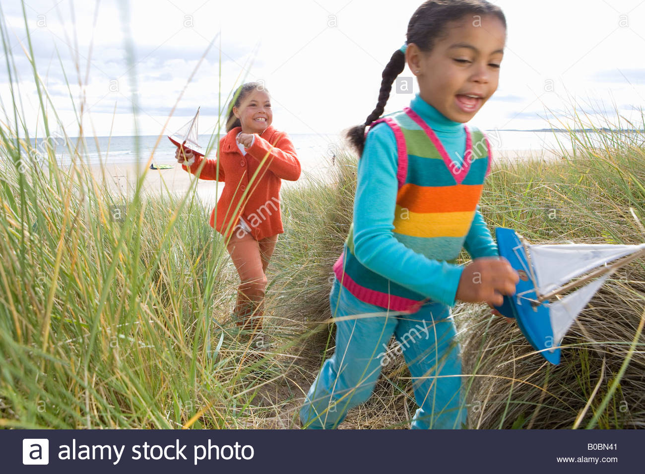 Sisters 5-9 with toy boats on sand dune blurred motion - Stock Image
