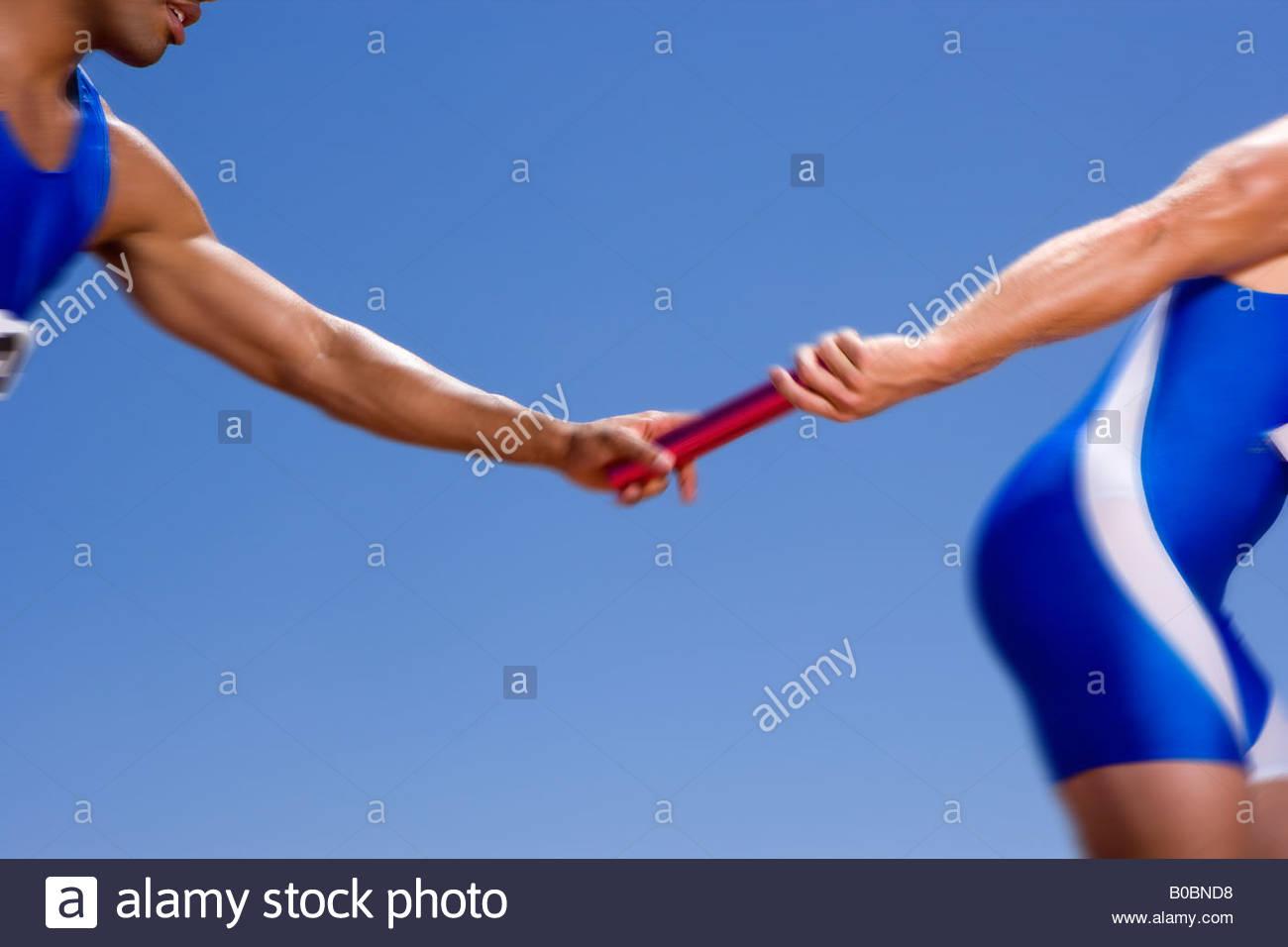 Relay athletes passing baton blurred motion - Stock Image