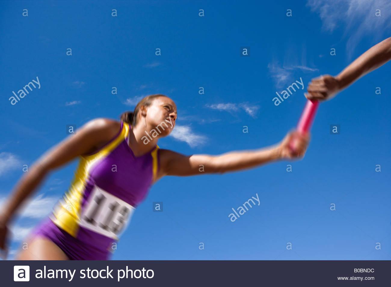 Female relay athletes passing baton blurred motion - Stock Image