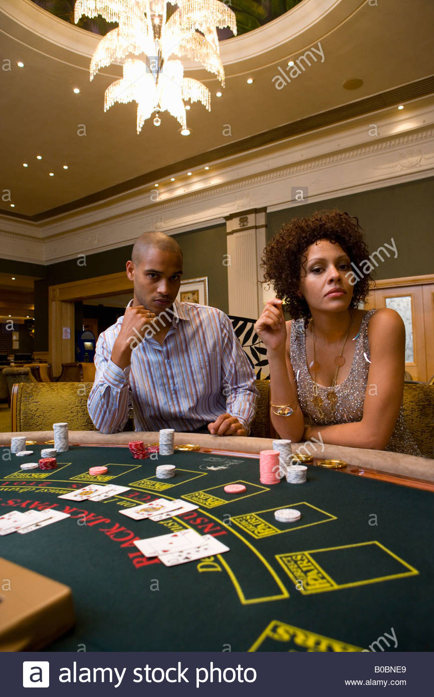 Young man and woman gambling at poker table, portrait Stock Photo