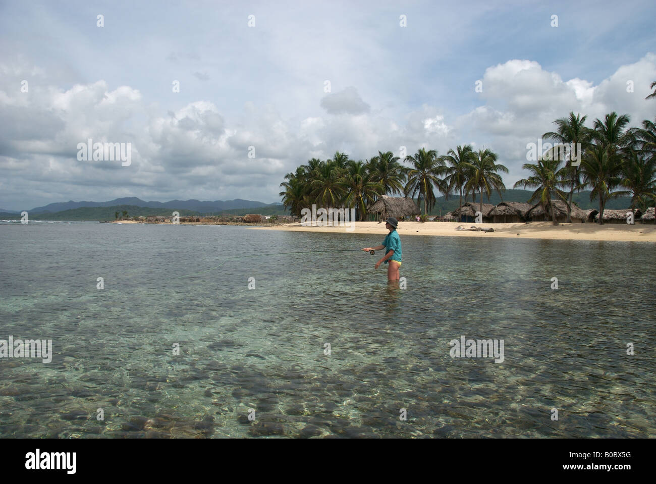 A woman fly fishing in front of cabanas on a remote island in the san blas islands panama - Stock Image