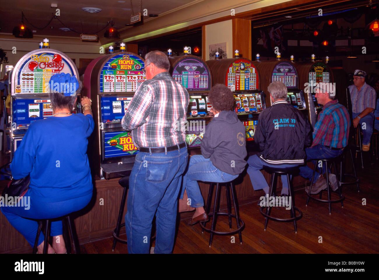 Gambling in Diamond Tooth Gertie's Gambling Hall, Dawson City, Yukon Territory, Canada - Gamblers playing Slot - Stock Image