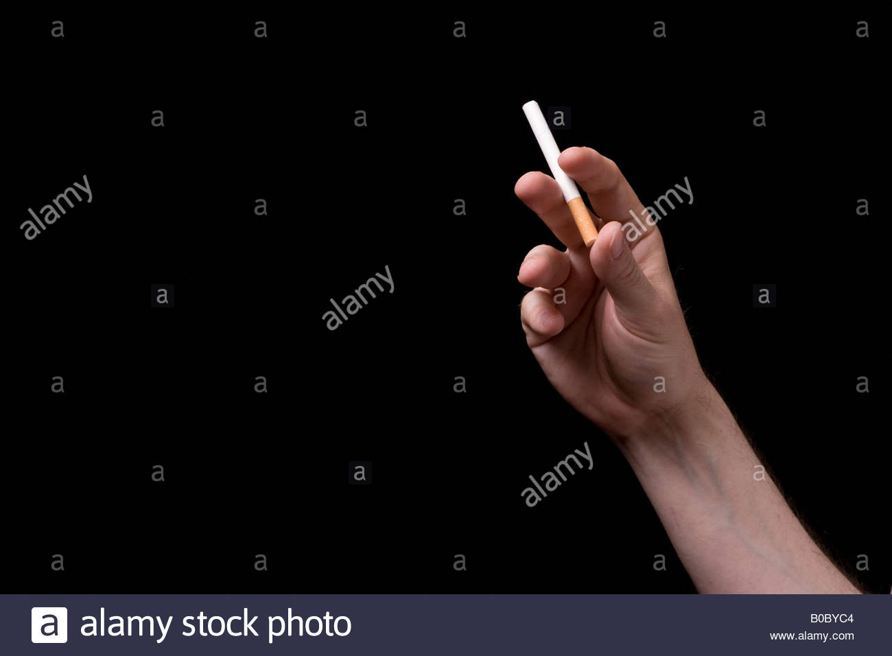 A hand holding a cigarette, UK. - Stock Image